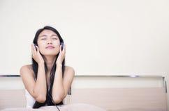 Aziatische vrouw die aan muziek luistert Royalty-vrije Stock Afbeeldingen