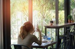 Aziatische vrouw die celtelefoon met behulp van terwijl het zitten in koffie met koffie a stock foto