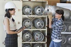 Aziatische vrouw die de vrouwelijke cilinder van het fabrieksarbeider dragende propaan bekijken Stock Fotografie