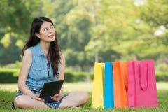 Aziatische vrouw die digitale tablet gebruiken die online het winkelen denken Royalty-vrije Stock Afbeelding