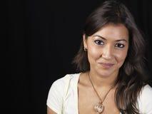 Aziatische vrouw die, donkere achtergrond glimlacht royalty-vrije stock foto's