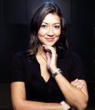 Aziatische vrouw die, donkere achtergrond glimlacht Stock Foto