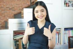 Aziatische vrouw die dubbele duimen in modern bureau opgeven stock fotografie