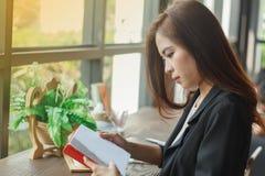Aziatische vrouw die een boek voor ontspanning lezen Stock Foto's