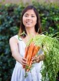 Aziatische vrouw die een bos van wortelen houden Stock Foto's