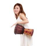 Aziatische vrouw die een djembe spelen Royalty-vrije Stock Afbeeldingen