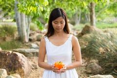 Aziatische vrouw die een gele groene paprika houden Stock Afbeelding