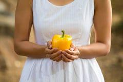 Aziatische vrouw die een gele groene paprika houden Royalty-vrije Stock Foto's