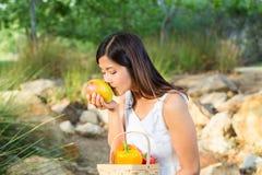 Aziatische vrouw die een mango ruiken terwijl het houden van een mand van groene paprika's en mango Stock Afbeeldingen