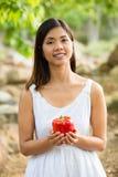 Aziatische vrouw die een rode groene paprika houden Stock Afbeelding