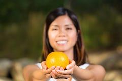Aziatische vrouw die een sinaasappel houden Stock Foto's