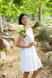 Aziatische vrouw die een witte bloem houden Royalty-vrije Stock Foto's
