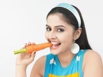 Aziatische vrouw die een wortel eet stock afbeeldingen