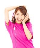 Aziatische vrouw die en van muziek in hoofdtelefoons genieten luisteren Royalty-vrije Stock Afbeeldingen