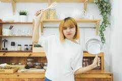 Aziatische vrouw die gezond voedsel maken die zich het gelukkige glimlachen in keuken bevinden die salade voorbereiden Mooie vrol Stock Afbeeldingen