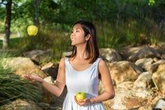 Aziatische vrouw die groene appelen in de lucht werpen Stock Afbeelding
