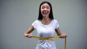 Aziatische vrouw die haar taille, tevreden met opleiding en dieet resultaten, pasvorm meten royalty-vrije stock foto's