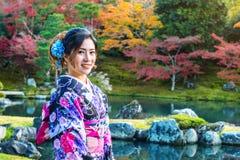 Aziatische vrouw die Japanse traditionele kimono in de herfstpark dragen japan stock afbeeldingen