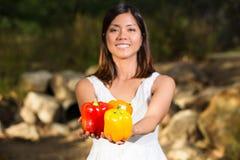 Aziatische vrouw die kleurrijke groene paprika's houden Royalty-vrije Stock Foto