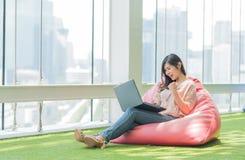 Aziatische vrouw die laptop gevierd succes gebruiken Royalty-vrije Stock Afbeelding