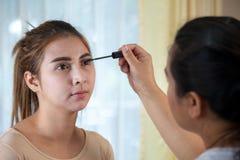 Aziatische vrouw die mascara op haar lange wimpers toepassen stock afbeeldingen
