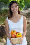 Aziatische vrouw die met een mango en een mand van groene paprika's en mango glimlachen Royalty-vrije Stock Afbeeldingen