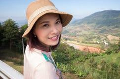 Aziatische vrouw die met hoed op mountian glimlachen Stock Foto's
