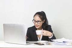 Aziatische vrouw die met laptop bij witte werkende lijst, ijverige professionele werkende vrouw het drinken koffie werken terwijl stock foto