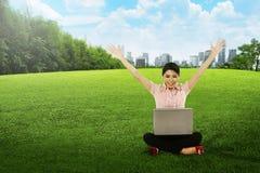 Aziatische vrouw die met laptop werken en op het gras zitten Stock Foto