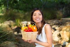 Aziatische vrouw die met mand van groene paprika's en mango glimlachen Stock Foto's