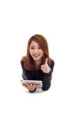 Aziatische vrouw die met tabletPC liggen en duim tonen. Royalty-vrije Stock Afbeeldingen