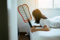 Aziatische vrouw die mugvliegemepper met behulp van thuis, Wijfje met mug elektrische netto racket in slaapkamer stock afbeelding