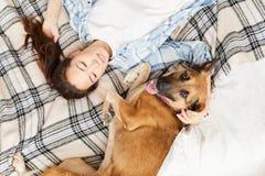 Aziatische Vrouw die op Bed met Hond liggen royalty-vrije stock afbeelding