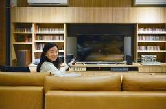 Aziatische vrouw die op lege het schermtv in woonkamer letten bij nacht Royalty-vrije Stock Afbeeldingen