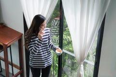 Aziatische vrouw die op mobiele telefoon spreken en zich bij koffie bevinden restaur royalty-vrije stock foto