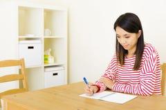 Aziatische vrouw die op notitieboekje schrijft stock foto's