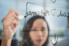 Aziatische vrouw die op transparante raad schrijven stock afbeelding