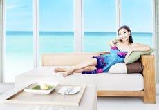 Aziatische vrouw die op TV let door het strand Stock Afbeeldingen
