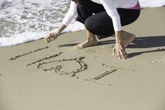 Aziatische vrouw die op zand met witte verpletterende golf schrijven Stock Afbeelding