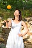 Aziatische vrouw die pret hebben die een sinaasappel in de lucht werpen Stock Afbeelding