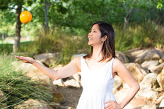 Aziatische vrouw die pret hebben die een sinaasappel in de lucht werpen Royalty-vrije Stock Fotografie