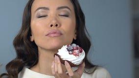 Aziatische vrouw die van smaak van smakelijke zoete cupcake met slagroom en fruit genieten stock video