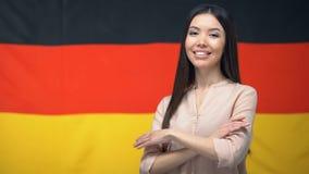 Aziatische vrouw die zich met die handen bevinden tegen Duitse vlag op achtergrond worden gekruist stock video