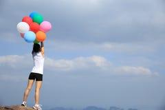 Aziatische vrouw die zich op berg piekrots bevinden met kleurrijke ballon Stock Fotografie