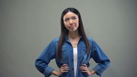 Aziatische vrouw die zich op grijze achtergrond bevinden, die keus tussen twee opties maken stock video
