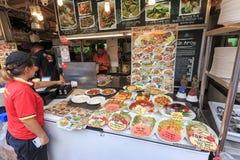 Aziatische vrouw die zich voor een voedselbox bevinden in het baaigebied, één van vele straatfoo stock foto