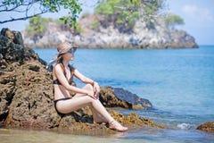 Aziatische vrouw die zonnebril in bikini het ontspannen op het strand dragen stock afbeeldingen