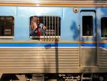 Aziatische vrouw die zonnebril dragen die uit van het venster kijken en zijn hand vaarwel van het vertrekken trein golven stock foto's