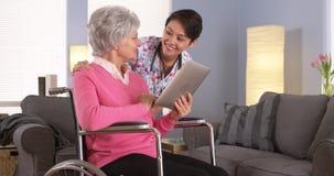 Aziatische vrouw en Bejaarde patiënt die met tablet spreken Stock Fotografie
