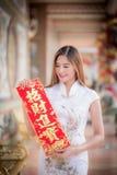 Aziatische vrouw in het Chinese 'sterke' couplet van de kledingsholding (Chinees Stock Afbeeldingen
